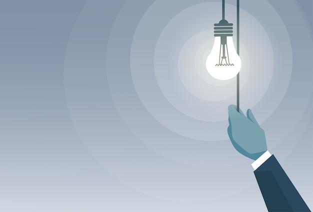 Geschäftsmann-hand, die glühlampe schaltet