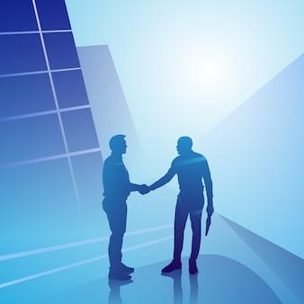 Geschäftsmann-handshake mit zwei schattenbildern, geschäftsmann-händedruckvereinbarungs-konzept