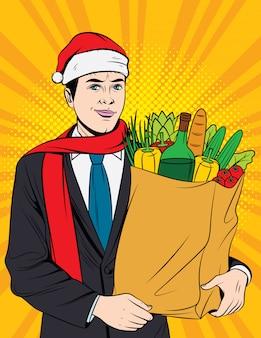 Geschäftsmann im roten weihnachtsmannhut, der lebensmitteleinkauf tut