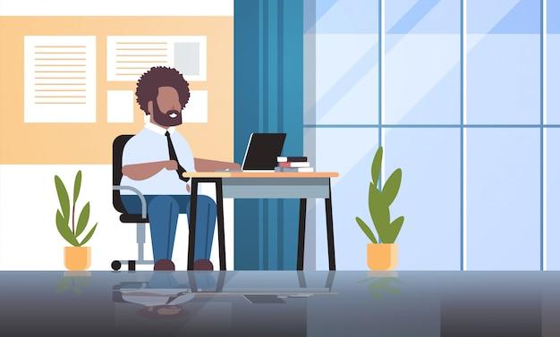 Geschäftsmann-manager, der laptop-fettgeschäftsmann-arbeiter-sitzarbeitsplatzkonzept verwendet