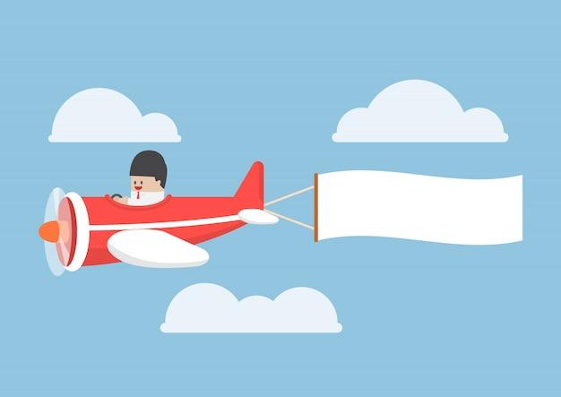 Geschäftsmann mit dem flugzeug mit banner fliegen