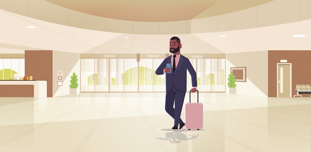 Geschäftsmann mit gepäck modernen empfangsbereich afroamerikaner geschäftsmann hält koffer kerl in der lobby zeitgenössischen hotelhalle interieur stehen
