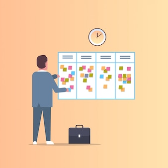Geschäftsmann plant seine arbeitsagenda wöchentliche besprechung zeitplan task board mit haftnotizen geschäftsplanung nachrichten ereignisse erinnerung und zeitplan konzept in voller länge flach