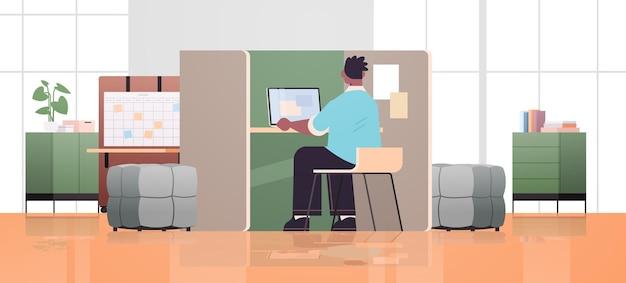 Geschäftsmann sitzt am arbeitsplatz geschäftsmann, der im kreativen coworking center arbeitet