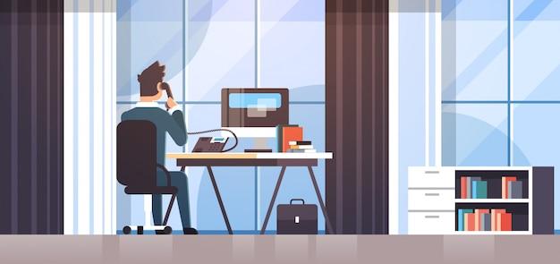 Geschäftsmann sitzt am arbeitsplatz schreibtisch rückansicht geschäftsmann mit computer beim sprechen auf festnetz telefon arbeitsprozess kreative büro interieur