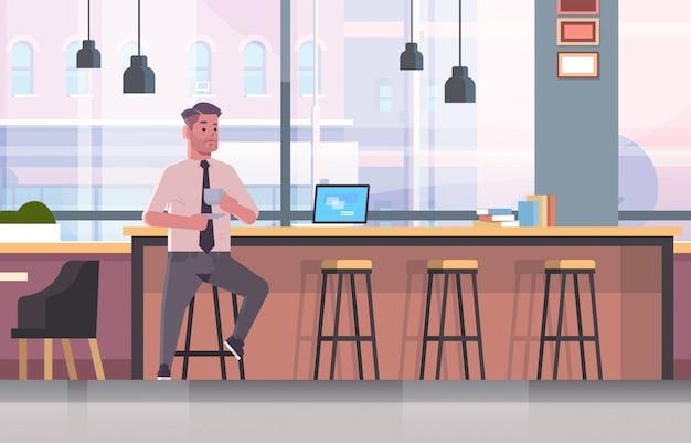 Geschäftsmann sitzt auf stuhl am bartheke mit laptop-kaffeepause-geschäftsmann, der cappuccino-modernes café-interieur trinkt