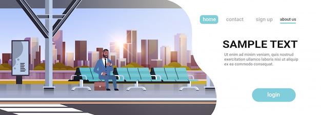 Geschäftsmann sitzt modernen bushaltestelle geschäftsmann mit koffer, der öffentliche verkehrsmittel auf flughafenstation stadtbildhintergrund horizontal in voller länge kopienraum wartet