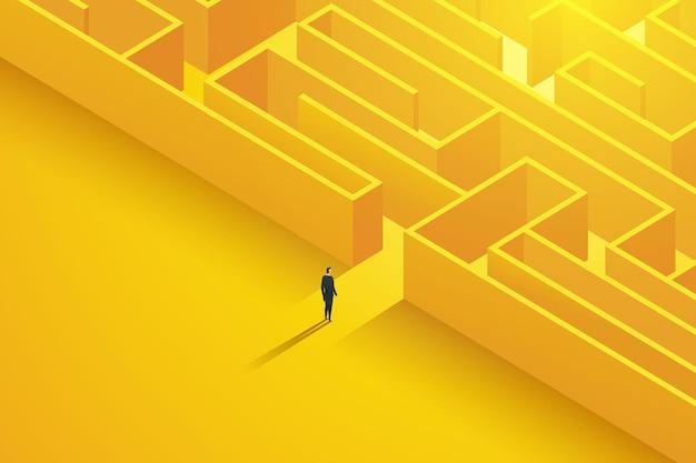 Geschäftsmann steht vor dem eingang zu einem großen komplexen labyrinth mit herausforderungen
