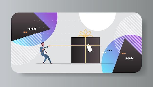 Geschäftsmann zieht große geschenkbox mit tag weihnachten neujahr winterferien feier konzept horizontale flache vektor-illustration in voller länge