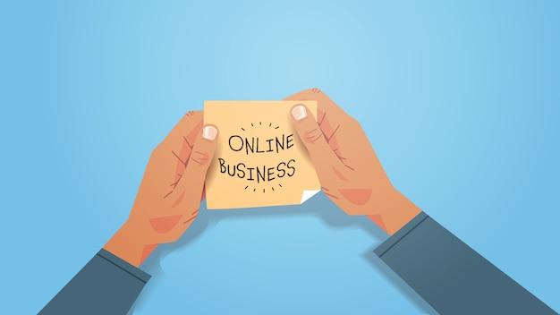 Geschäftsmannhände halten gelben aufkleber online-geschäft auf haftnotizpapier geschrieben