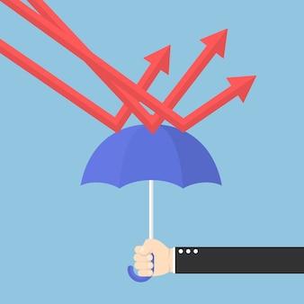 Geschäftsmannhand unter verwendung des regenschirmes, zum des abwärtstrenddiagramms zu schützen
