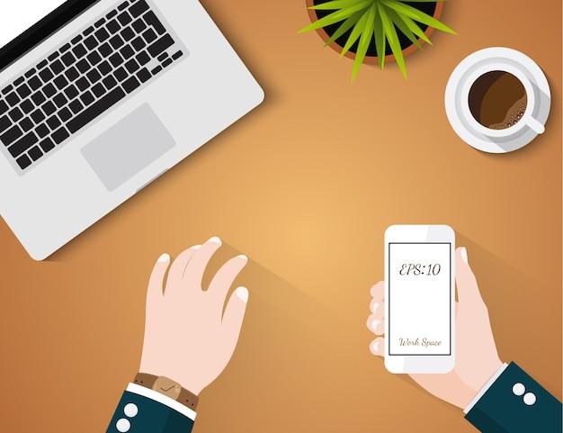 Geschäftsvektor-konzeptarbeitsplatz mit dem laptopkaffee und hand, die smartphone halten