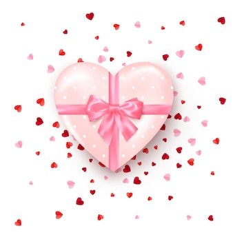 Geschenk in herzförmiger schachtel mit rosa seidenschleife