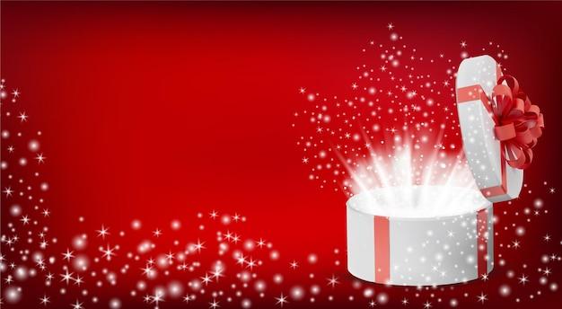 Geschenk weiße box in einem roten band und schleife oben. geöffnete runde weihnachtsschachtel mit leuchtenden glitzern im inneren.