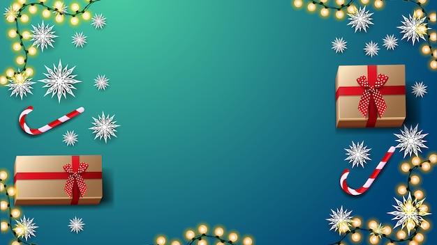 Geschenke, candys stock, papierschneeflocken und girlande auf blauer tabelle, draufsicht. hintergrund