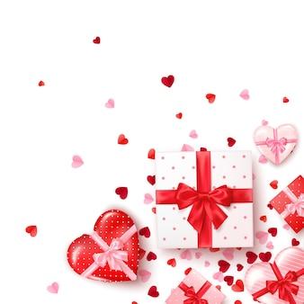 Geschenke in quadratischen und herzförmigen schachteln mit seidenband und schleife. geschenk zum valentinstag dekoriert konfetti. vorlage für banner oder grußkarte.