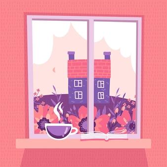 Geschlossenes fenster mit blick auf die frühlingslandschaft. rosa himmel mit wolken, wiese, altes landhaus. eine tasse kaffee und ein offenes buch liegen auf der fensterbank.