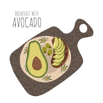Geschnittenes sandwich mit avocado in einer platte auf einem schneidebrett