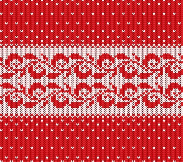 Gestrickte weihnachtsrote und weiße nahtlose mit blumenverzierung mit fallendem schnee. weihnachten stricken winter pullover textur design.