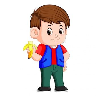 Gesunder kleiner junge, der banane isst