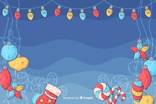 Gezeichnetes design des weihnachtshintergrundes in der hand