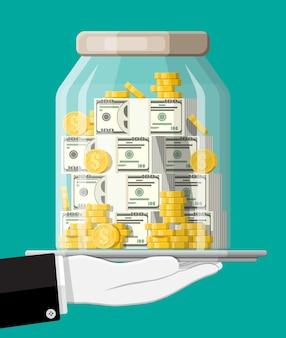 Glasgeldglas voller goldmünzen und banknoten auf tablett