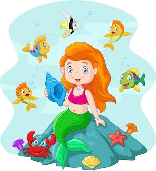 Glückliche kleine Meerjungfrau, die auf dem Felsen sitzt