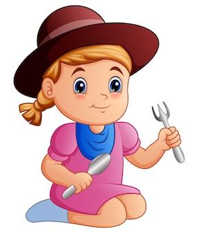 Glückliches kleines Mädchen der Karikatur, das einen Löffel und eine Gabel hält