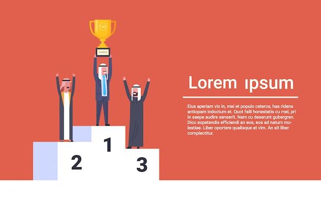 Glückliche arabische geschäftsleute, die auf sieger-podium moslemischem geschäftsmann leader holding golden cup corporate success concept stehen