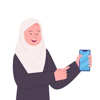 Glückliche arabische hijab-frau, die auf smartphone zeigt