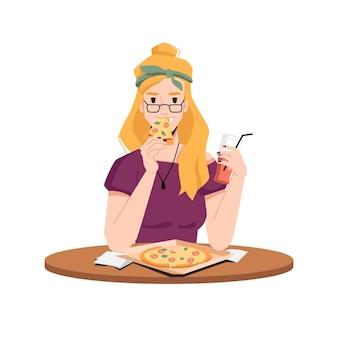 Glückliche blonde frau isst pizza und trinkt saft aus glas mit isoliertem strohhalm