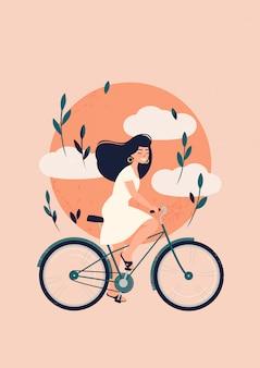 Glückliche brünette frau fährt fahrrad vor der sonne mit wolken