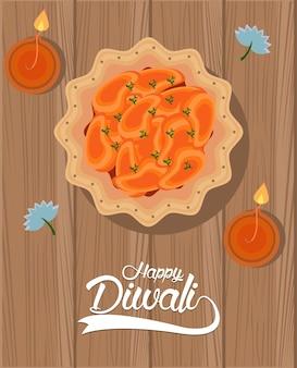 Glückliche diwali-feier mit zwei kerzen und essen im hölzernen hintergrund