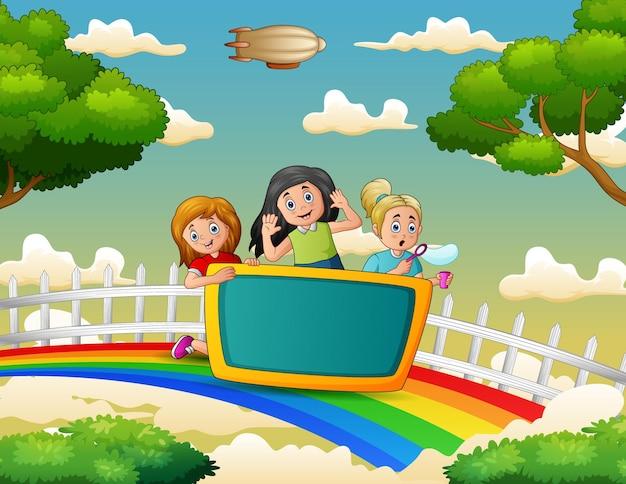 Glückliche drei mädchen über dem bunten regenbogen