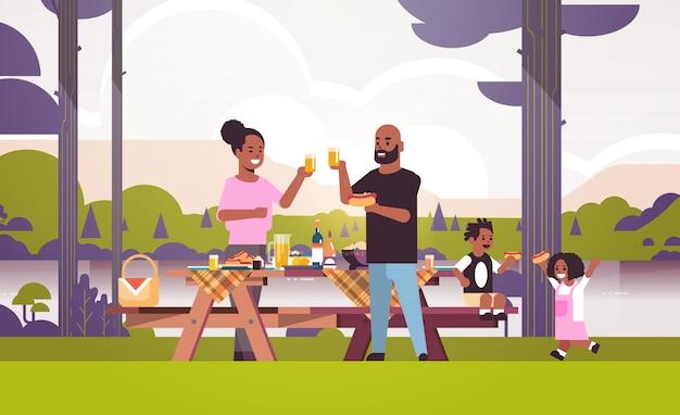 Glückliche eltern und kinder, die hot dogs essen saft afroamerikanerfamilie essen picknickwochenende konzept flussufer landschaft hintergrund flach in voller länge horizontal