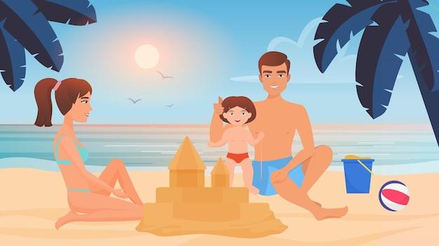 Glückliche familie baut sandburg zusammen mit sand am tropischen strand des sandkastens