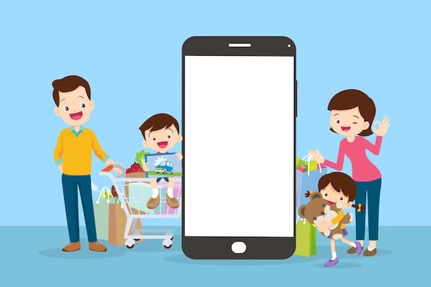 Glückliche familie beim online-einkauf von lebensmitteln mit der mobilen app auf ihrem smartphone