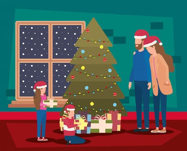 Glückliche familie der frohen weihnachten, die mit kiefer feiert