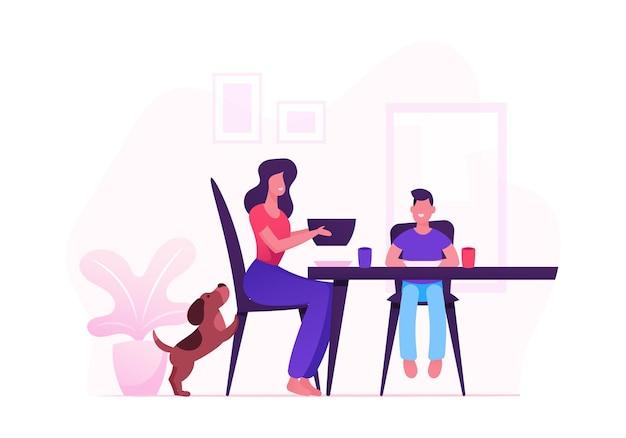 Glückliche familie der mutter, des kleinen kindes und des haustieres, das abendessen mit essen am tisch sitzt