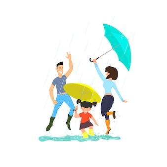 Glückliche familie, die in den pfützen mit regenschirmen im regen springt.