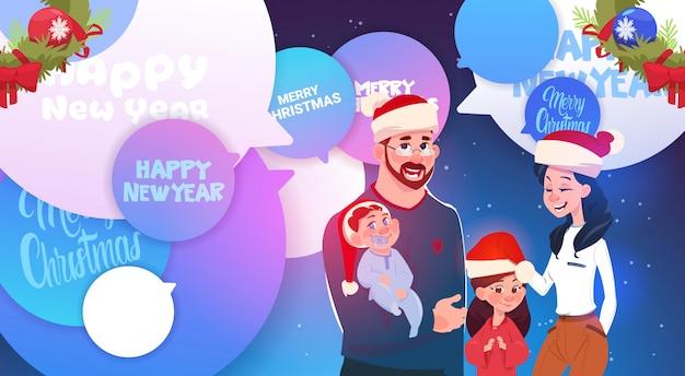 Glückliche familie, die santa hats über nachrichten der frohen weihnachten und des neuen jahres auf chat-blasen trägt