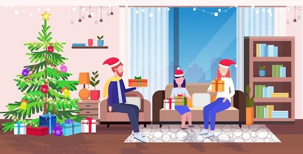 Glückliche familie in santa, die auf couch nahe tannenbaumweihnachtsfeiertagsfeierkonzept sitzt eltern und tochter, die geschenkboxen wohnzimmerinnenraum halten