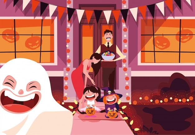 Glückliche familie mit süßigkeiten in der halloween-nachtfeier
