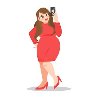 Glückliche fette dame im roten pulloverkleid nehmen ein selfie durch handy auf weißem hintergrund
