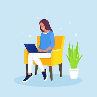 Glückliche frau, die auf lehnsessel sitzt und an laptop arbeitet. freiberuflich, online-studium, homeoffice, coworking space konzept