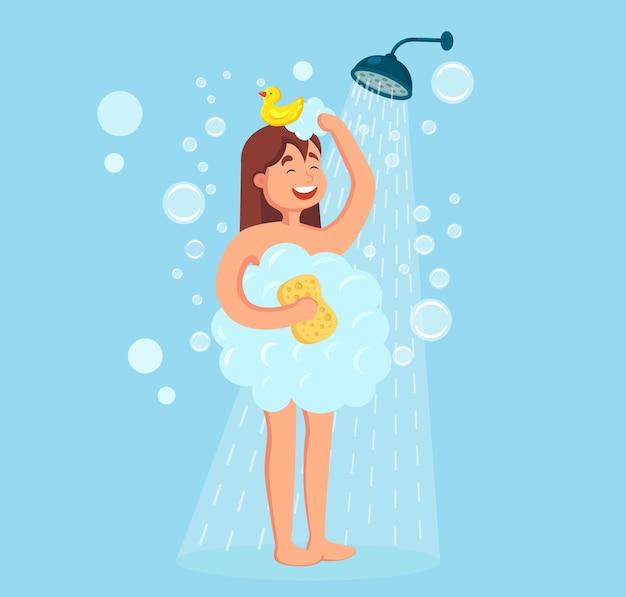 Glückliche frau, die dusche mit gummiente im badezimmer nimmt. waschen sie kopf, haare, körper und haut mit shampoo, seife und schwamm