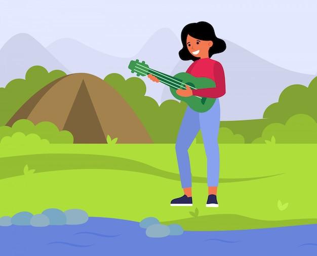 Glückliche frau, die gitarre in der landschaft spielt