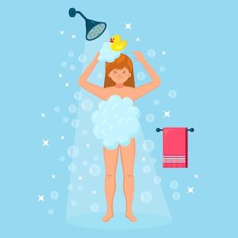 Glückliche frau, die im badezimmer mit gummiente duscht. haare, körper mit shampoo, seife, schwamm waschen