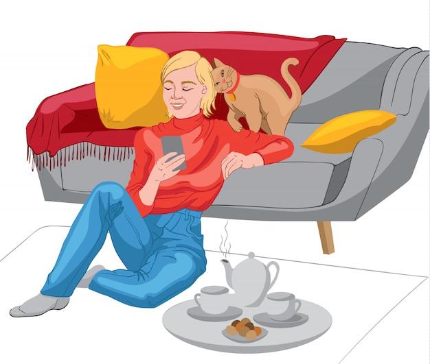 Glückliche frau gekleidet in rotem pullover und in jeans, die in ihrem telefon schauen, während sie auf dem boden sitzen und sich auf das sofa lehnen. teekanne, teetassen und kekse auf einem teller. katze mit rotem kragen