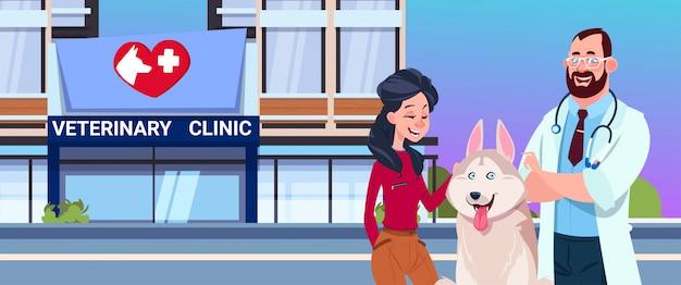 Glückliche frau mit hund und tierarzt doctor over veterinary clinic exterior